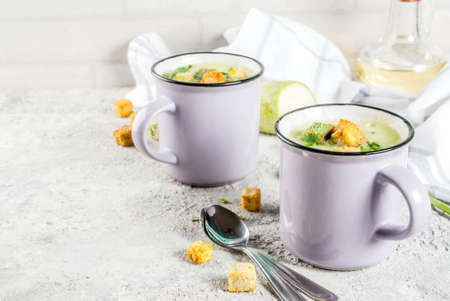 Two portions of homemade zucchini creamy soup with bread crumbs in mugs on a light concrete background. 写真素材