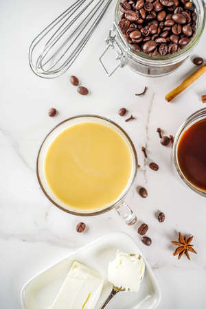 Trendy ketogenic diet food, Bulletproof coffee with milk and butter, white marble background copy space top view