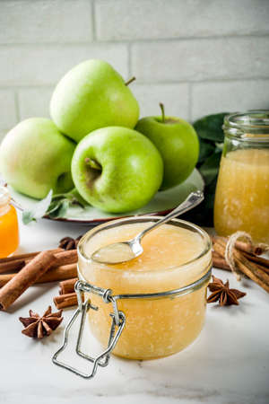 Homemade apple jam or sauce, with green apples and spices, white marble background copy space
