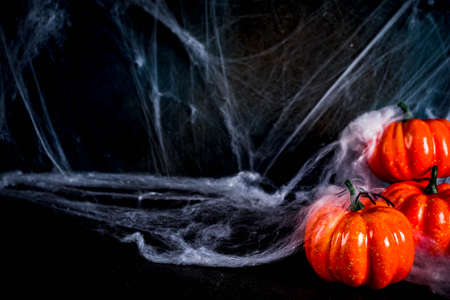 Halloween concept, a dark background old wall with cobwebs and pumpkins, greeting card background