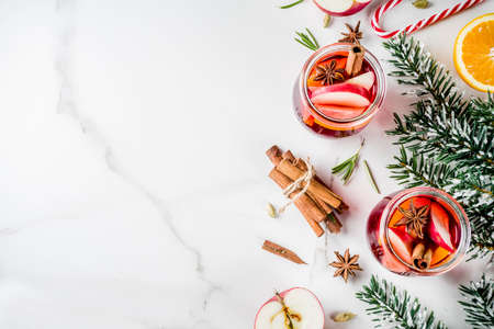 Traditional winter drinks, white and red mulled wine cocktail,  with white and red wine, spices, apple, orange. On white marble background copy space Stock Photo