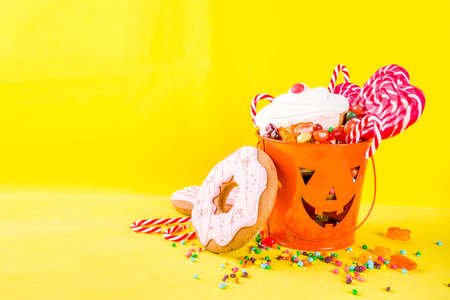 Halloween sweets concept, bucket in the form of a festive pumpkin, full of sweets and candies, cookies, jellies, desserts, bright yellow background top view copy space Stock Photo