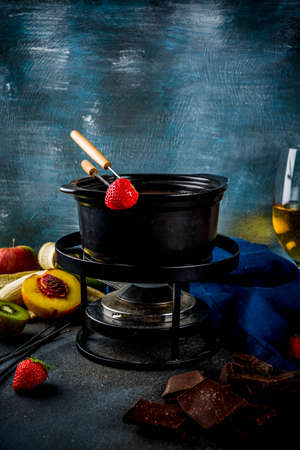 Chocolate fondue in traditional fondue pot, with forks, white wine, assorted various berries and fruit, copy space Stock Photo