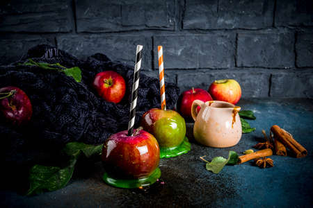 Traditional autumn delicacy, apples in caramel glaze. On a dark background, with apples, leaves, caramel sauce and a warm blanket. Copy space for text Banque d'images - 108109660