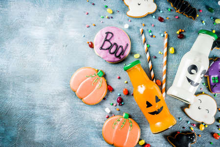 Kids treats for Halloween, funny homemade glazed cookies, various candies milk and juice in monster bottle, blue concrete background copy space top view Stock Photo