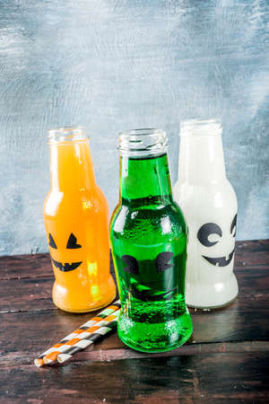 Party drinks for Halloween, three milk and juice in monster bottle, blue concrete background copy space top view
