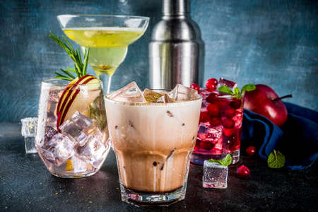 Various autumn winter seasonal alcohol cocktail Apple Rosemary, Cranberry vodka, Ginger lemon ale,  Almande Horchata,  Cacao, dark blue background copy space Stok Fotoğraf