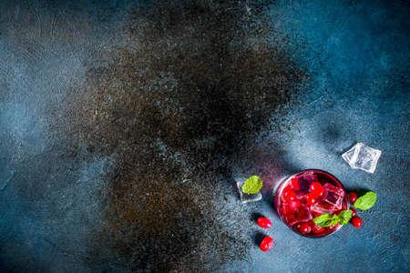 Autumn winter seasonal alcohol cocktail Cranberry vodka, dark blue background copy space top view