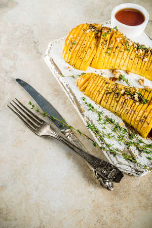 Simple autumn domestic recipes, roasted hasselback butternut squash pumpkin with thyme, honey and maple syrup, on light background copy space top view