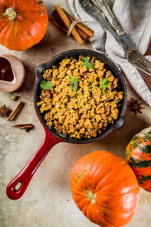 Homemade autumn pastries, pumpkin crumble pie in a cast-iron frying pan, light stone background, copy space top view Stock Photo