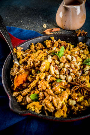 Homemade autumn pastries, pumpkin crumble pie in a cast-iron frying pan, dark blue concrete background, copy space top view