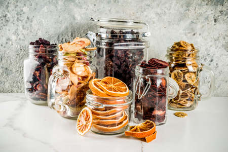 Home herfst oogst, gedroogd fruit en bessen in glazen potten voor conserven, aardbeien, frambozen, appels, bananen, sinaasappels, lichte betonnen achtergrond, kopie ruimte