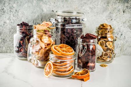 Inicio cosecha de otoño, frutos secos y bayas en frascos de vidrio para conservas enlatadas, fresas, frambuesas, manzanas, plátanos, naranjas, fondo de hormigón claro, espacio de copia