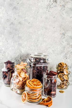 Home autumn harvest, dried fruits and berries in glass jars for canned preserves, strawberries, raspberries, apples, bananas, oranges, light concrete background, copy space