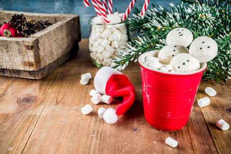 Hot chocolate with creative marshmallow in the form of snowmen with Christmas decorations in a box, wooden background, copy space Stock Photo