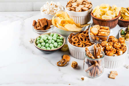 Variation different unhealthy snacks crackers, sweet salted popcorn, tortillas, nuts, straws, bretsels, white marble background copy space Stockfoto