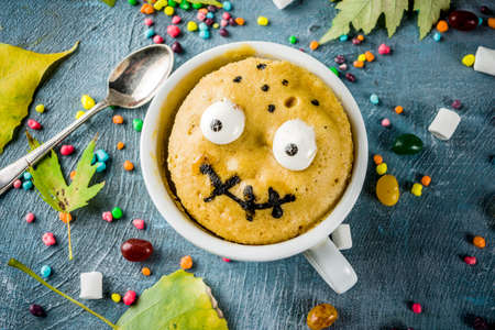 Kids Halloween food idea, funny mug cake decorate like monster face with marshmallow eyes and mouth painted with edible marker, blue background with sweets and autumn leaves, copy space