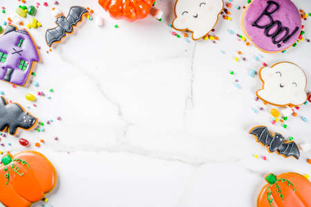 Traditional Halloween baked pastry, funny cookies and candies for children's treat - ghost, pumpkins, black cat, bats, witch house. White background, top view copy space Archivio Fotografico - 108943455