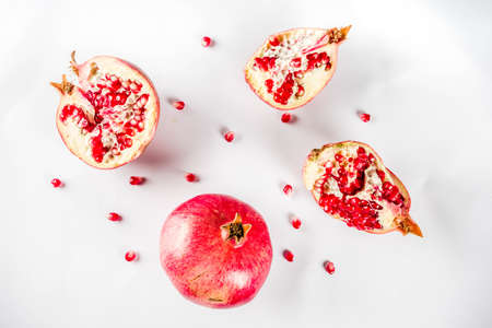 Fresh raw juicy whole and broken pomegranate on white background, top view flatlay creative layout Stock Photo