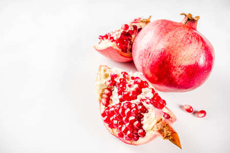 Fresh raw juicy whole and broken pomegranate on white background, top view flatlay creative layout Фото со стока