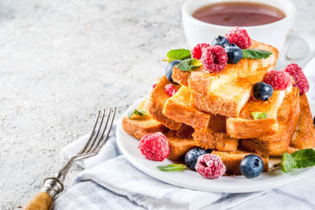 Healthy summer breakfast, baked french toasted bread sticks with fresh berry and honey, morning light grey stone background copy space Reklamní fotografie