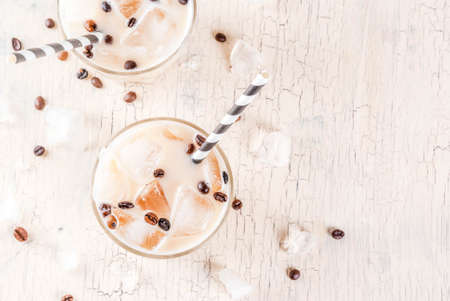 Summer cold Iced coffee frappe with milk and ice cubes, light concrete background copy space above Stock Photo
