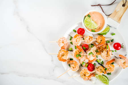 Seafood kebabs, shrimp skewers with sauce, lime, spring onions and cherry tomatoes, white marble background copy space top view