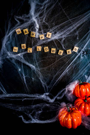 Halloween concept, a dark background old wall with cobwebs and pumpkins