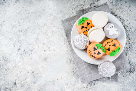 Creative idea for Halloween treats, funny macaron cookies decorated spider cobweb, ghost, pumpkin monster