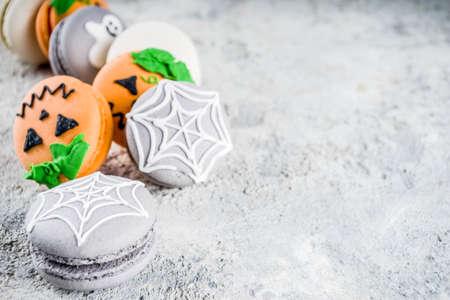 Creative idea for Halloween treats, funny macaron cookies decorated spider cobweb, ghost, pumpkin monster