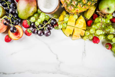 Various tropic fruits, summer vitamins concept, coconut, pineapple, grapes, peach, nectarine, strawberry, apples, mango, banana. top view copy space