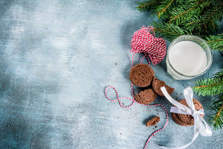 Festive Christmas greeting card background with natural Fir Spruce branches, chocolate cookies, milk glass. Christmas treat for Santa Claus, light blue background copy space