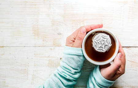 Halloween treats concept, Girl drinking hot chocolate with marshmallow decorate spider cobweb, hands in the picture, top view, copy space Stockfoto