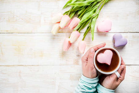 Girl drinking hot chocolate with marshmallows in the shape of hearts, Valentines Day celebration, hands in the picture, top view, copy space Stock Photo