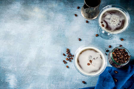 Coffee drink ideas, espresso martini cocktail, two glasses on blue concrete background copy space