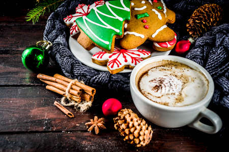 Traditional christmas sweet treats, colorful sugar glazed homemade gingerbread cookies with xmas tree, decoration, spices and coffee latte mud on classic wooden background copy space top view