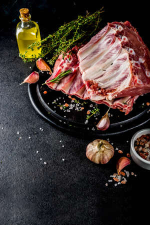 Raw meat, pork ribs with herbs and spices, black stone background copy space