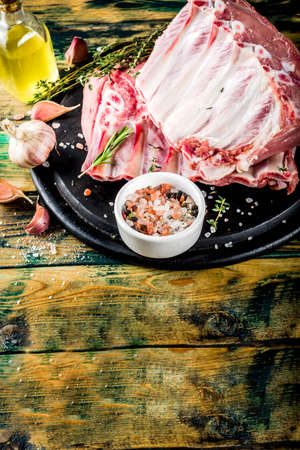 Raw meat, pork ribs with herbs and spices, old wooden background copy space Stock Photo