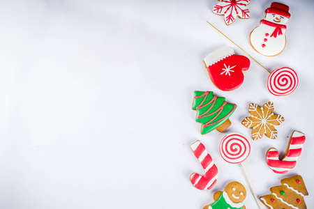 Various traditional colorful sugar glazed christmas gingerbread cookies, on white background top view copy space