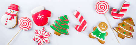 Various traditional colorful sugar glazed christmas gingerbread cookies, on white background top view copy space banner