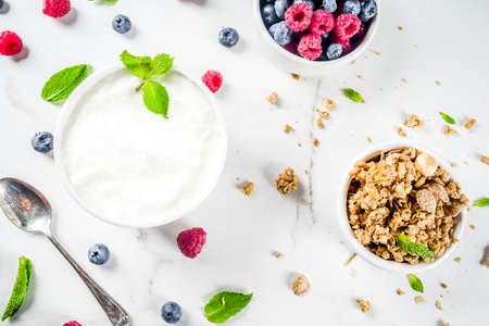 Healthy snack or breakfast idea, homemade organic greek yogurt with granola, raspberries, mint, blueberries on white marble table top view.
