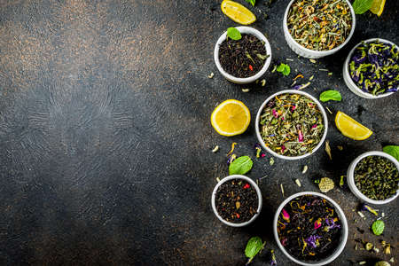 Assortment of various dry tea - classic black and green, flower, fruit, berry and herbal tea blends, with lemon and mint, White marble background copy space top view Reklamní fotografie