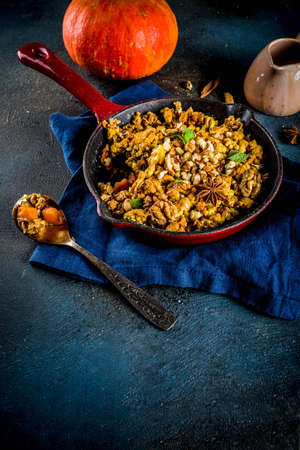 Homemade autumn pastries, pumpkin crumble pie in a cast-iron frying pan, dark blue concrete background, copy space top view Stock Photo - 109763313