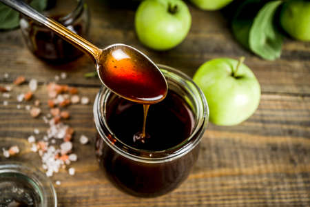 Home cooked dark salted classic caramel sauce, with green apples, wooden and dark blue background,
