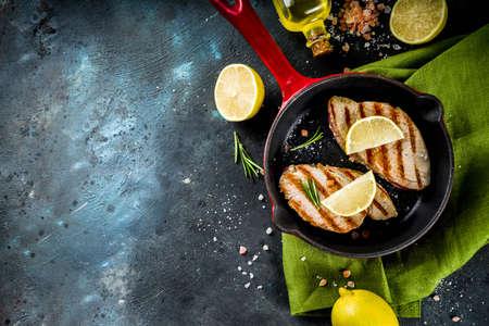 Gegrilde tonijnsteaks met citroen en kruiden op koekenpan, donkerblauwe betonnen achtergrond kopie ruimte bovenaanzicht Stockfoto