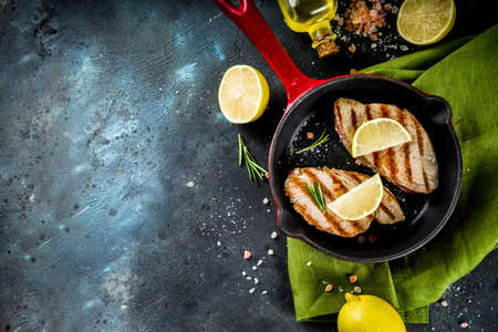 Grilled tuna fish steaks with lemon and spices on frying pan, dark blue concrete background copy space top view