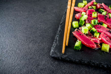 Tuna sashimi poke with raw fresh fish, cucumber, black sesame seeds and soy sauce, black stone background copy space Stock Photo
