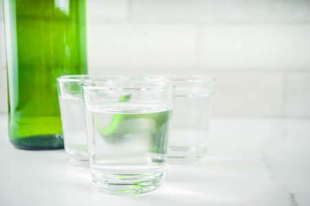 Traditional korean alcohol drink soju on light concrete background copy space