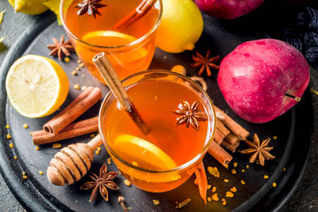 Two cups of autumn winter hot spicy tea with red apples, lemons, cinnamon, anise, honey, Dark rusty background copy space Stock Photo