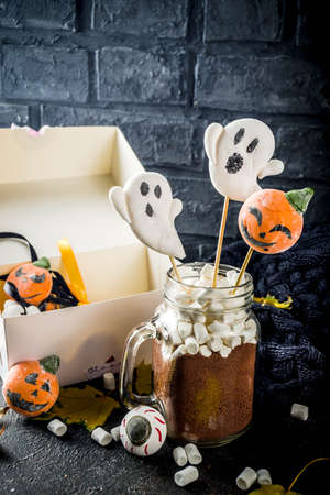 Funny idea for Halloween party, hot chocolate with decorative with marshmallows in shape of a ghost, pumpkin, monster, eyes,dark background copy space Stockfoto